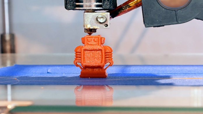 A plastic robot being printed by a 3d printer