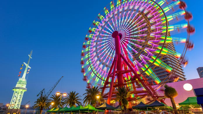 A colorfully lit ferris wheel set in front of an evening sky