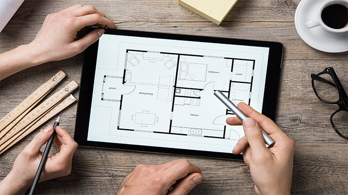 Hands examining groundplan of house on tablet device