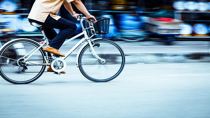 A person with blue pants and brown shoes rides a white bicycle