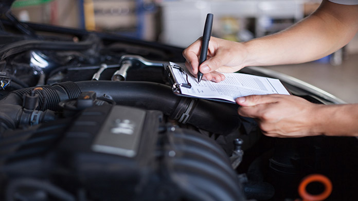 https://cdn2.howtostartanllc.comA person writing on a clipboard over top a car engine.