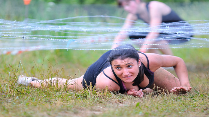 Woman climbing under barbed wire