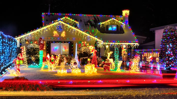 A Large House Covered With Christmas Lights
