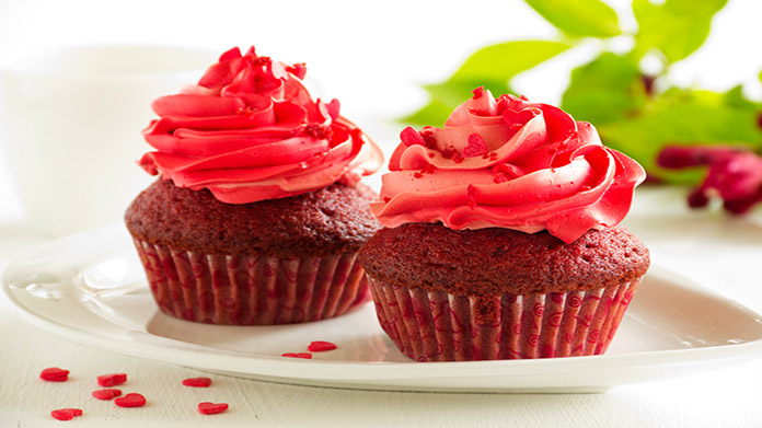 Two red velvet cupcakes with red frosting on white plate