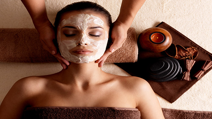 A woman with lotion on her face laying down on her back while another person's hands massage her neck