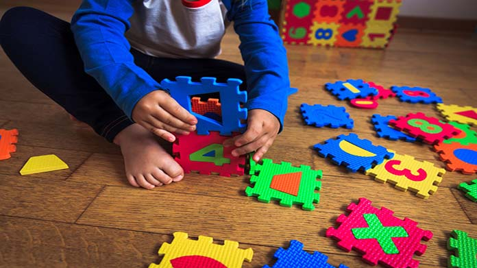 Child playing with colorful numbered puzzle pieces.