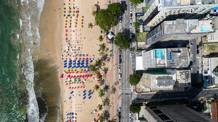 https://cdn2.howtostartanllc.comAn aerial shot of buildings and people on a beach