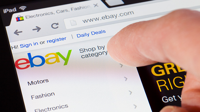 Woman holding a tablet with the eBay app loaded