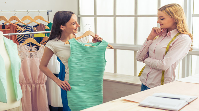 https://cdn2.howtostartanllc.comA woman holding a dress while another woman watches her