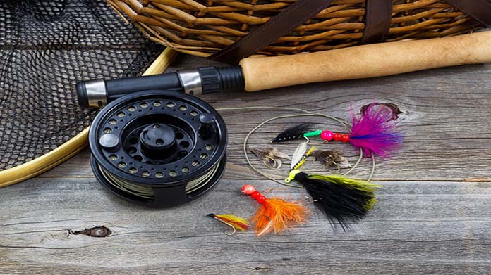 https://cdn2.howtostartanllc.comFly fishing rod and reel set on a table with colorful flies.