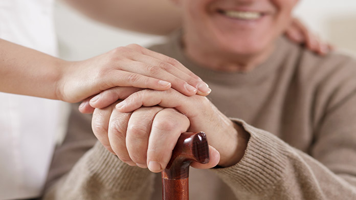 An older persons hand being held by an in home care taker