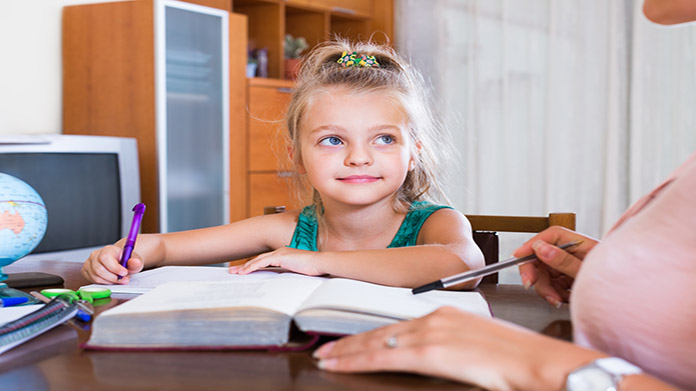 Child doing homework looking at her tutor