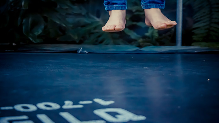 Feet suspended in air above a trampoline surface