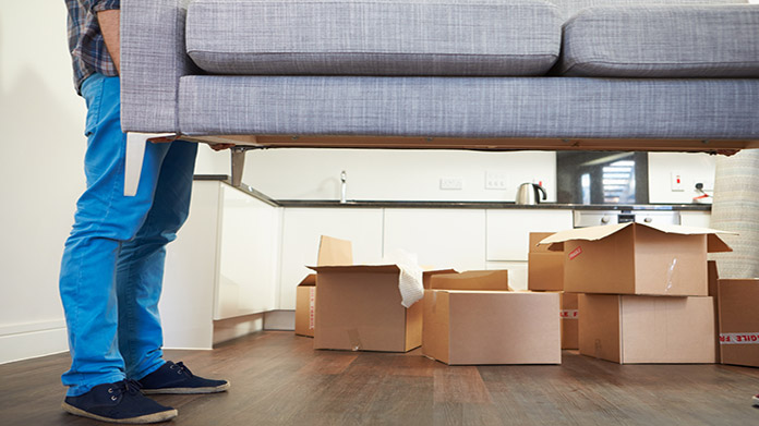 https://cdn2.howtostartanllc.comA man lifting a light blue couch with moving boxes in the background
