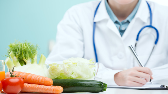 A group of vegetables next to a man in a lab coat.