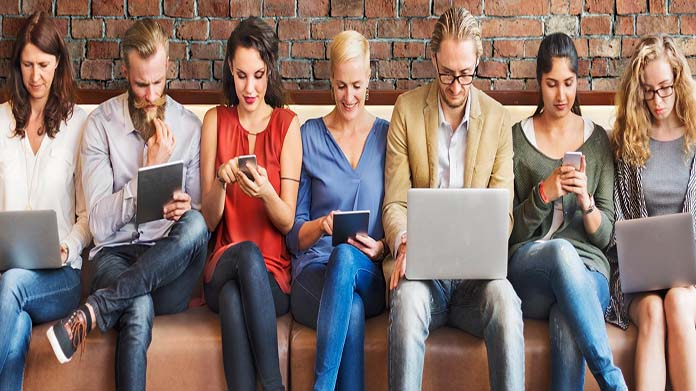 https://cdn2.howtostartanllc.comA row of people using phones and computers