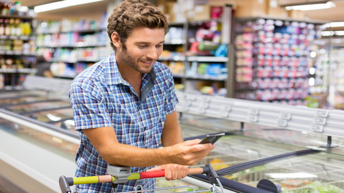 Man pushing grocery cart while looking at his phone