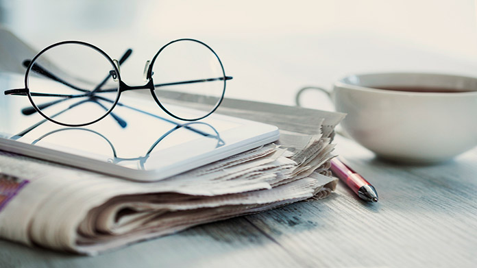 https://cdn2.howtostartanllc.comA newspaper, a pair of glasses, and a coffee mug on a table