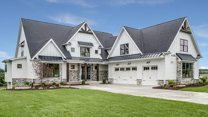 A bird's eye view photo of a large white house with a pool in the backyard