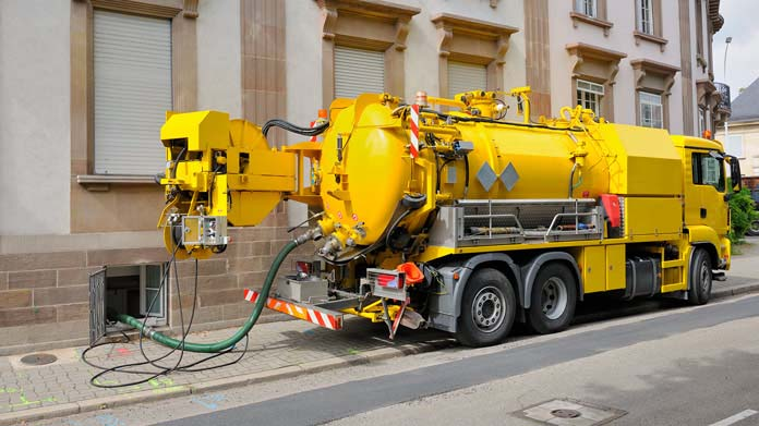https://cdn2.howtostartanllc.comA yellow septic tank truck in front of a building