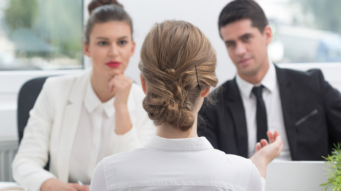 The back of a woman's head who is being interviewed for a job