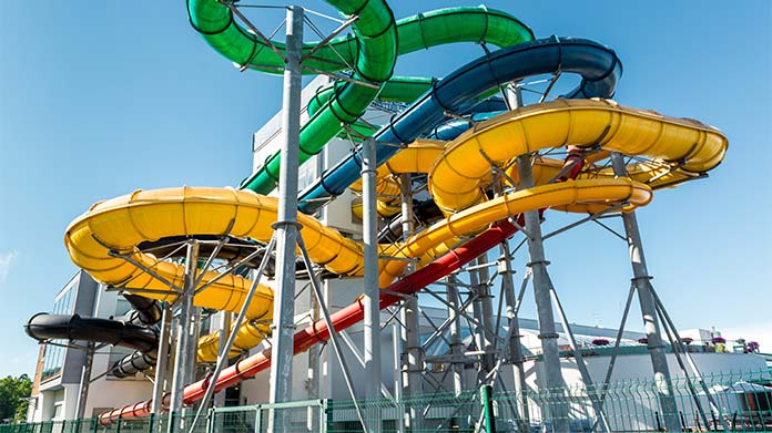https://cdn2.howtostartanllc.comA large colorful waterslide inside a waterpark