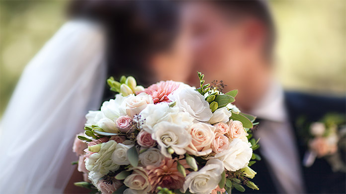 Bride and groom kissing out-of-focus behind and in-focus bouquet
