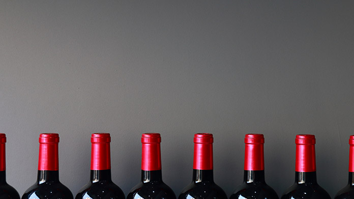 https://cdn2.howtostartanllc.comA line of wine bottles against a grey wall
