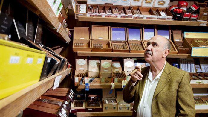 An old, well-dressed, mustachioed man browses the contents of a humidor at a cigar shop.