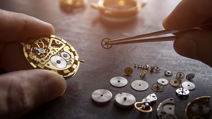 https://cdn2.howtostartanllc.comThe pieces of a pocket watch laid out on a table