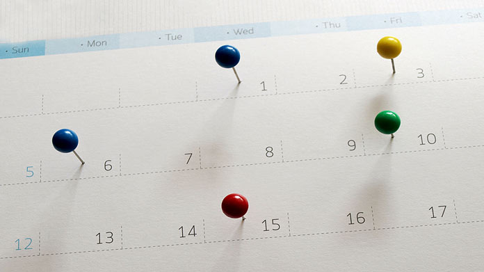 Calendar with colored push pins stuck into it