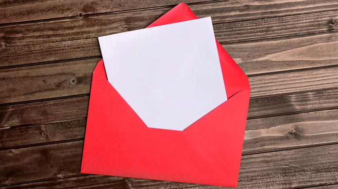 https://cdn2.howtostartanllc.comA white card halfway out of a red envelope on a wooden table