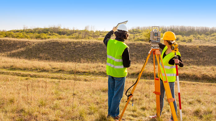 https://cdn2.howtostartanllc.comTwo people using land surveying equipment in a field