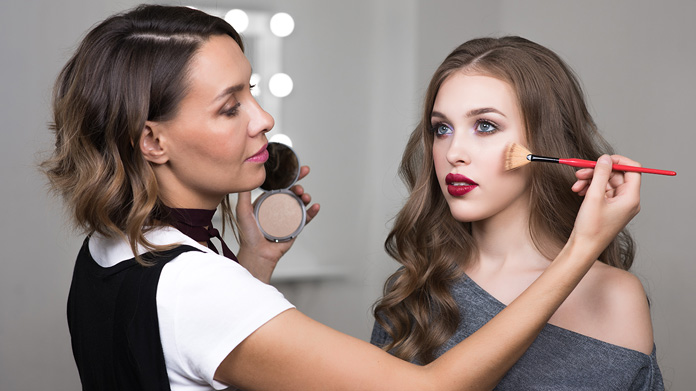 Makeup artist applying makup to a model with a brush