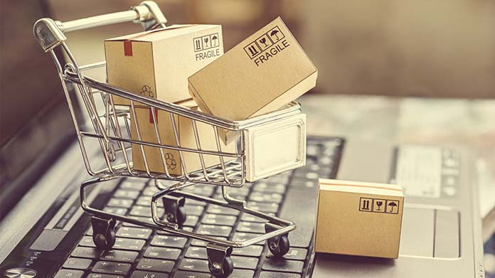 https://cdn2.howtostartanllc.comA small grocery cart filled with boxes sitting on a laptop
