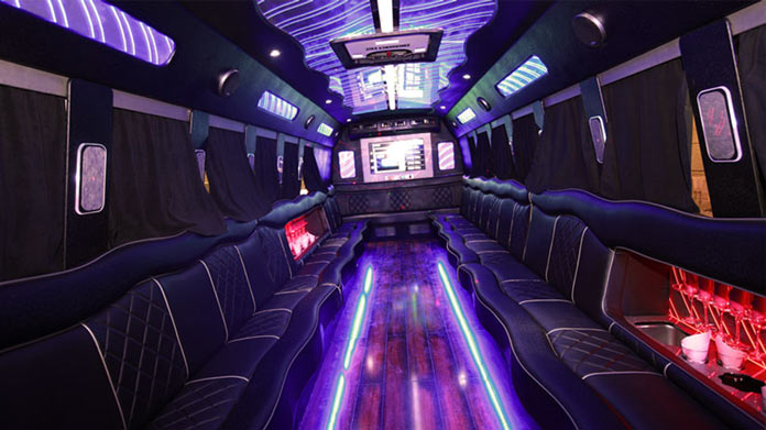 Interior of a party bus, lit with neon lights with full-length couches on either side.