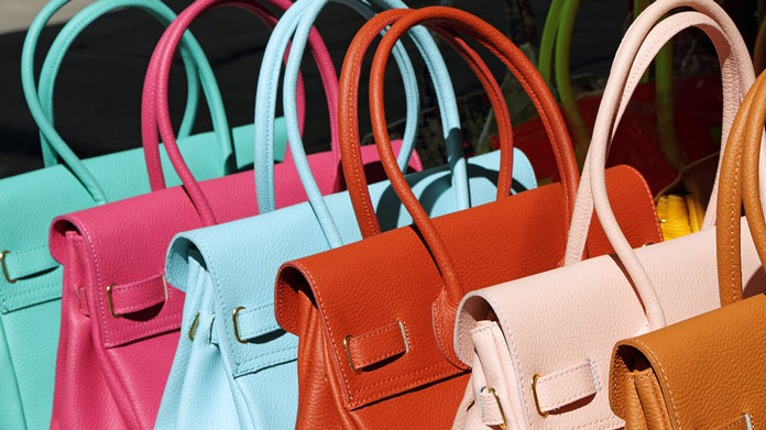 https://cdn2.howtostartanllc.comA row of different colored purses