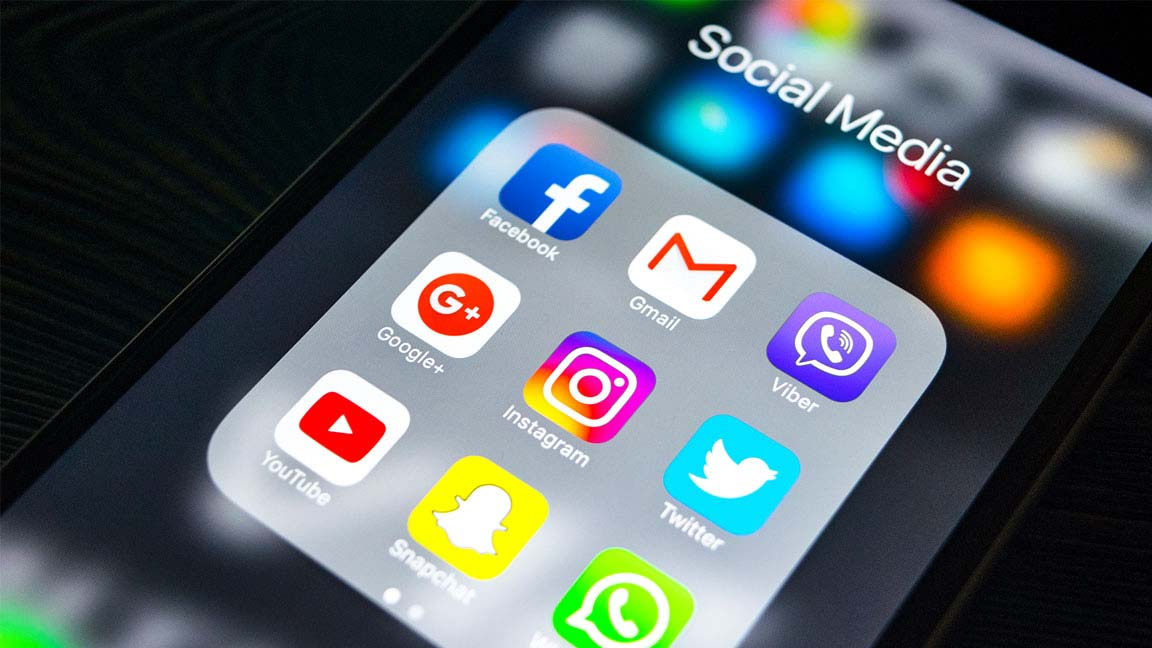 Closeup photo of an iPhone with many social media app icons