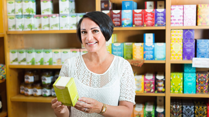 https://cdn2.howtostartanllc.comA woman holding a box of supplements in front of multiple shelves filled with boxes of various supplements