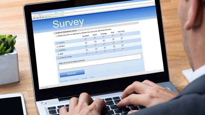 A man talking a survey on his computer