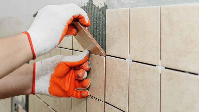 A person in white and orange gloves placing tile on a wall