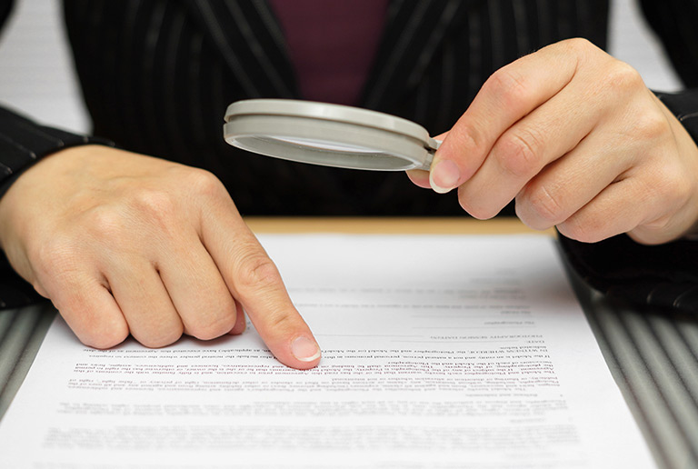 Hands holding a magnifying glass over a legal document with small text