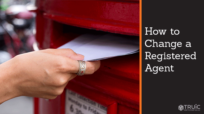 hand putting a letter into red post office mailbox